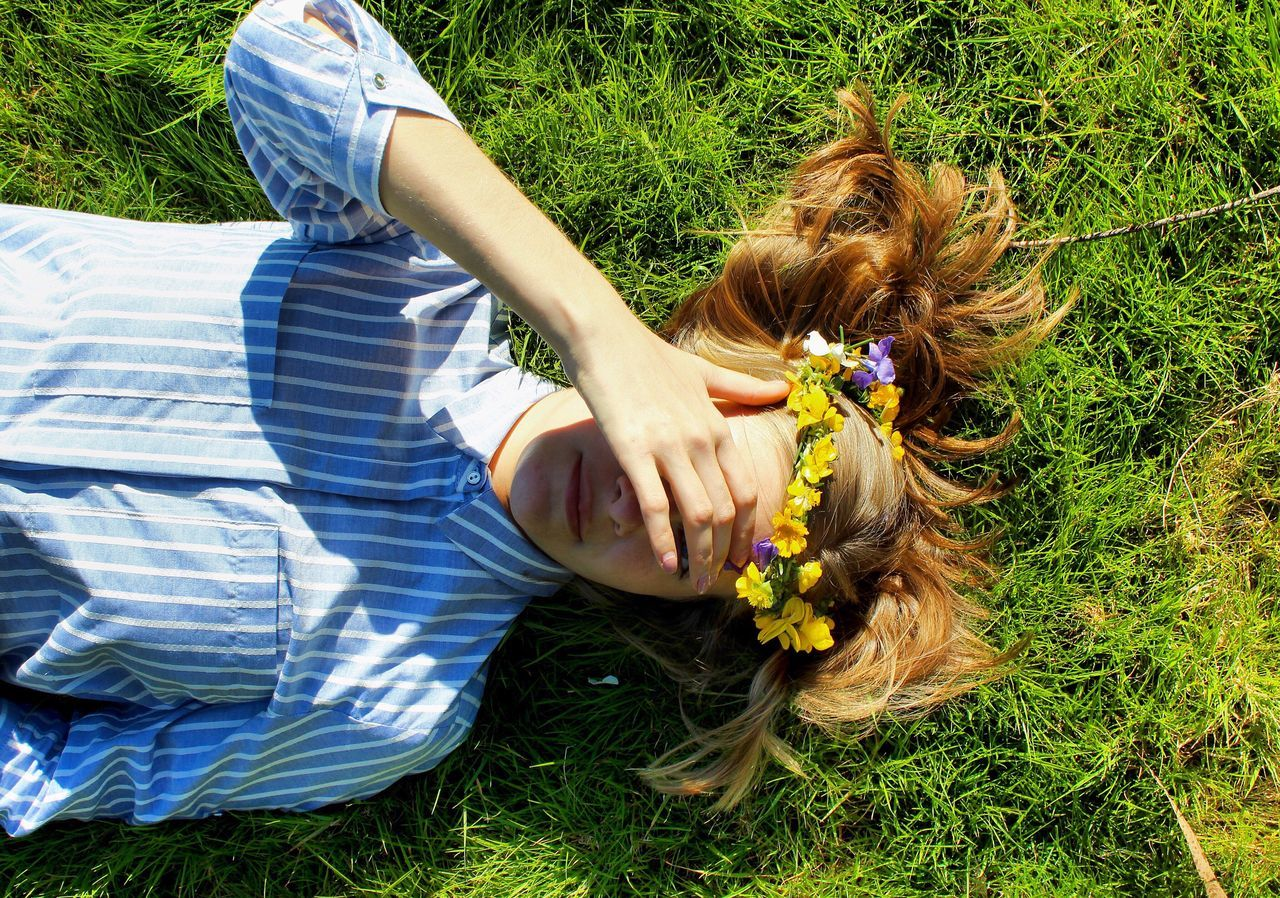 grass, real people, one person, lying down, high angle view, leisure activity, day, field, outdoors, sitting, young adult, young women, relaxation, lifestyles, low section, women, nature, full length, human hand, people