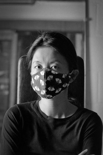 Portrait of teenage girl covering face at home