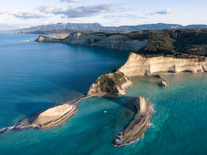 Aerial view of sea and rock formation against sky