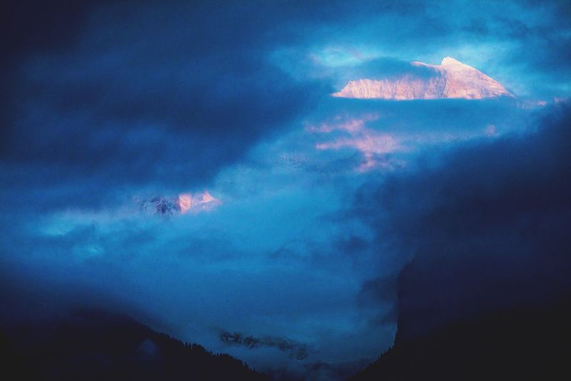 Low angle view of storm clouds over mountain