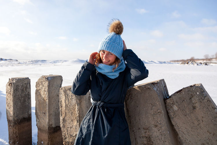 A young woman in a blue knitting hat, black coat enjoys winter nature, walking on the frozen sea