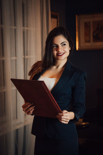 Smiling Standing Indoors  One Person Young Adult Looking At Camera Portrait Front View Holding Women Adult Young Women Waist Up Three Quarter Length Happiness Digital Tablet Real People Emotion Teeth Wireless Technology Hairstyle Beautiful Woman