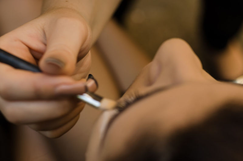 Cropped Hand Of Beautician Applying Make-Up To Woman In Spa