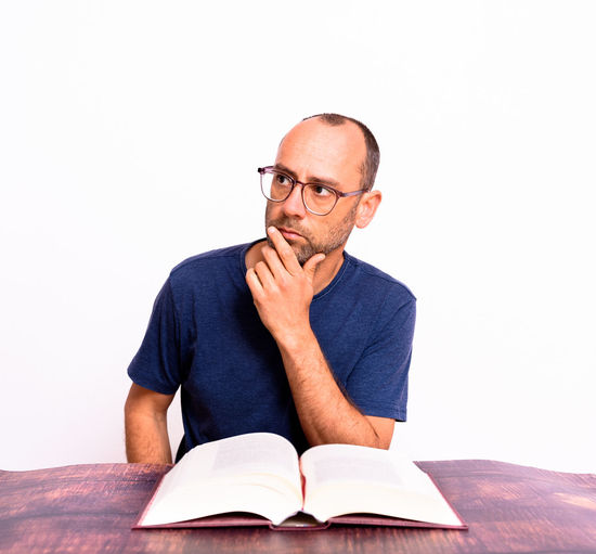 Portrait of man sitting against white background