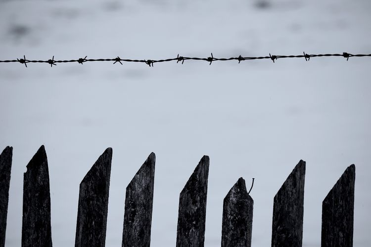Close-up of barbed wire over fence against sky