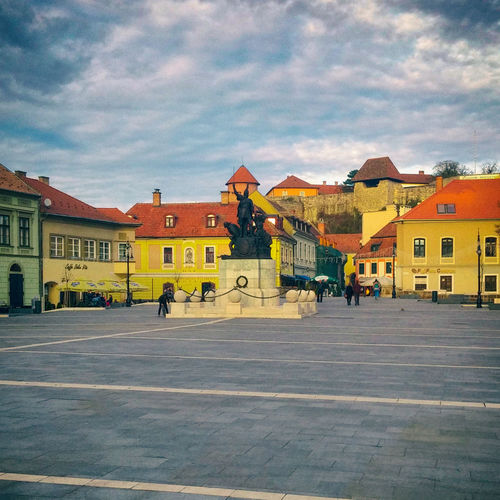 Eger. Architecture Building Building Exterior Built Structure City City Life City Street Cloud Cloud - Sky Cloudy Day Eger Façade Group Of People Lifestyles Main Square Medium Group Of People Nik Collection Outdoors Residential Building Sky The Way Forward Travel Destinations Unrecognizable Person