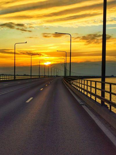Road by sea against orange sky