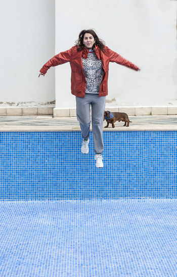 Full Length One Person Front View Lifestyles Leisure Activity Young Adult Jumping Pool Real People Swimming Pool Mid-air Emotion Happiness Young Women Human Arm Casual Clothing Standing Looking At Camera Arms Raised Warm Clothing Beautiful Woman