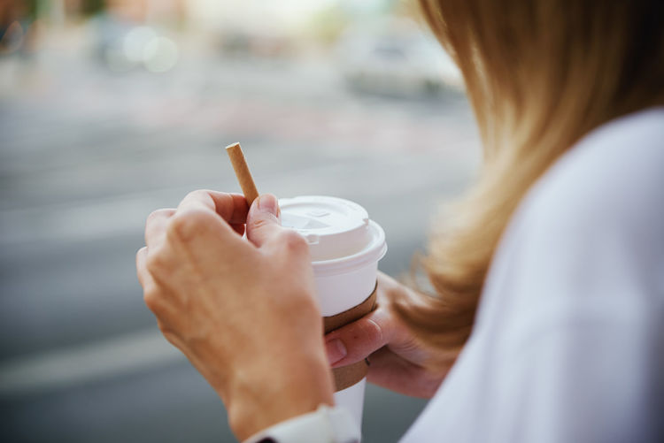 Woman holds paper coffee cup at city street