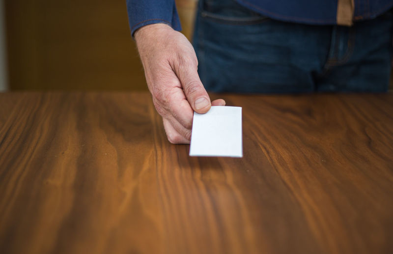 Midsection of person holding paper over table