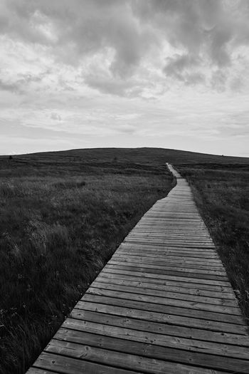 Boardwalk leading towards landscape against sky