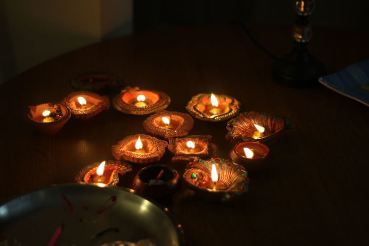 Burning Candle Diwali Diya - Oil Lamp Flame Illuminated In A Row Indoors  Large Group Of Objects Night No People Oil Lamp Tea Light Tradition Traditional Festival