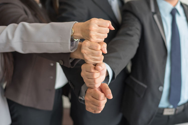 Midsection Of Business People Stacking Hands In Office