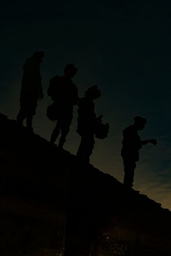 Low angle view of silhouette people standing on rock