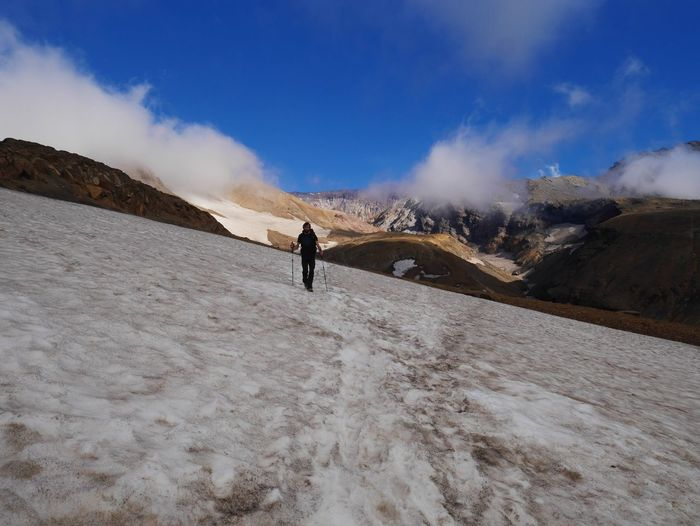 Hiker walking on snow covered mountain against sky