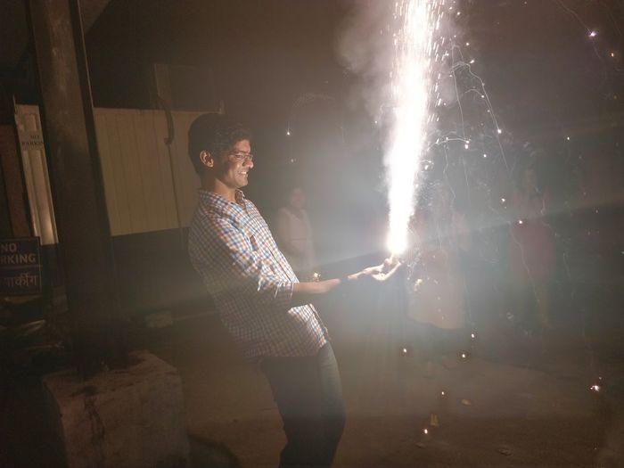 Man holding firework at night
