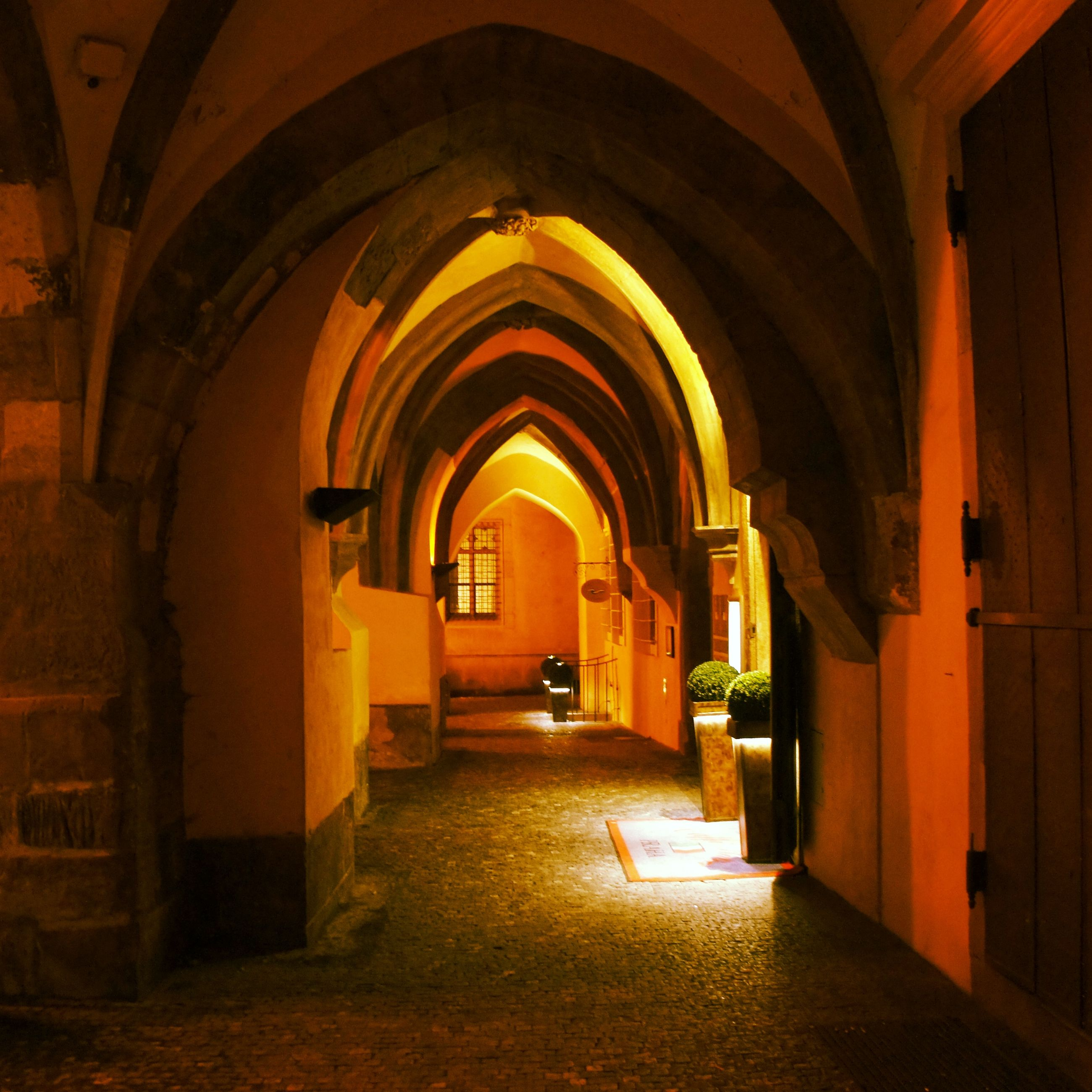 arch, architecture, indoors, built structure, religion, place of worship, the way forward, spirituality, illuminated, corridor, church, archway, entrance, history, building exterior, architectural column, pew, empty