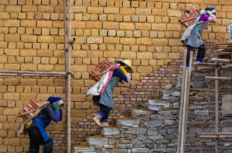 Architecture Brick Wall Casual Clothing Women Full Length Standing Brick Wall People Real People Togetherness Built Structure Females Girls Stone Wall Outdoors Sister Three Workers