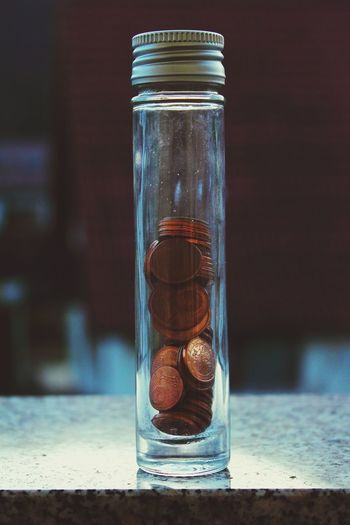 Close-up of coins in glass jar on table