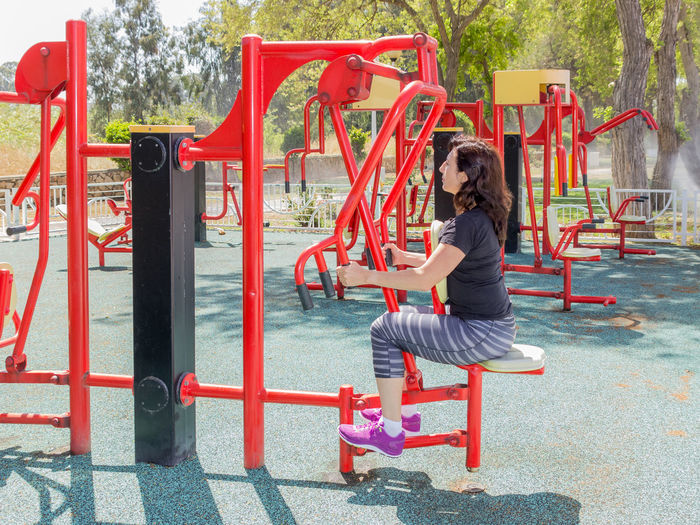 Young female athlete exercising at outdoor gym