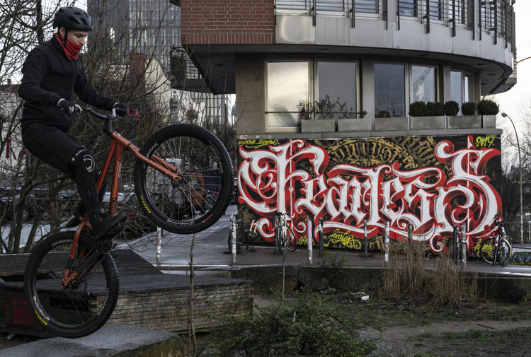 Fearless... Bicycle Built Structure Building Exterior One Person Text City Real People Building Red Wheel Outdoors Men Day Communication Streetphotography Unrecognizable Person Grafitti Hamburg Hansestadt Hamburg Artistic Urban Scene Cityscape Sport Exceptional Photographs Urbanphotography Streetwise Photography The Art Of Street Photography The Street Photographer - 2019 EyeEm Awards