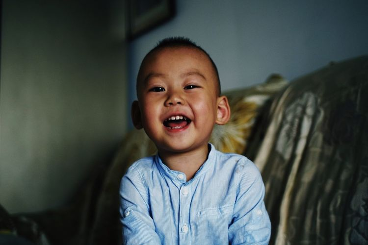 Portrait of cute cheerful boy sitting on sofa at home