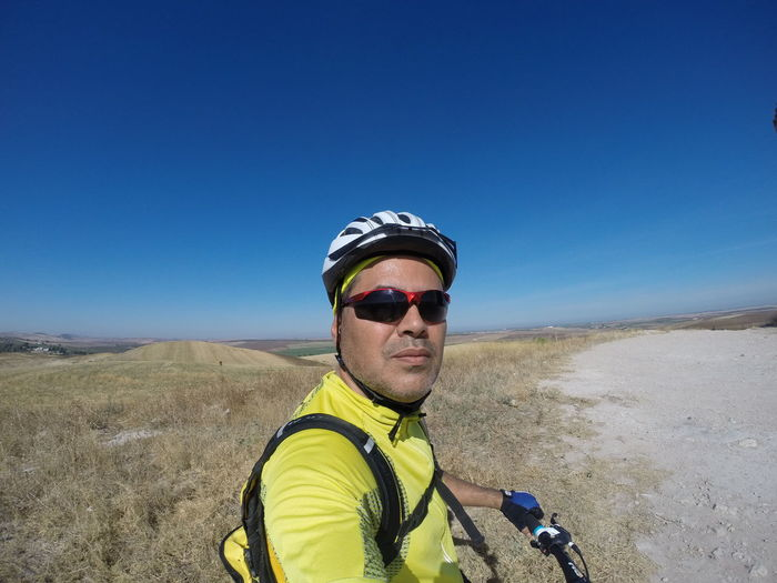 Side view portrait of man riding bicycle on field against blue sky