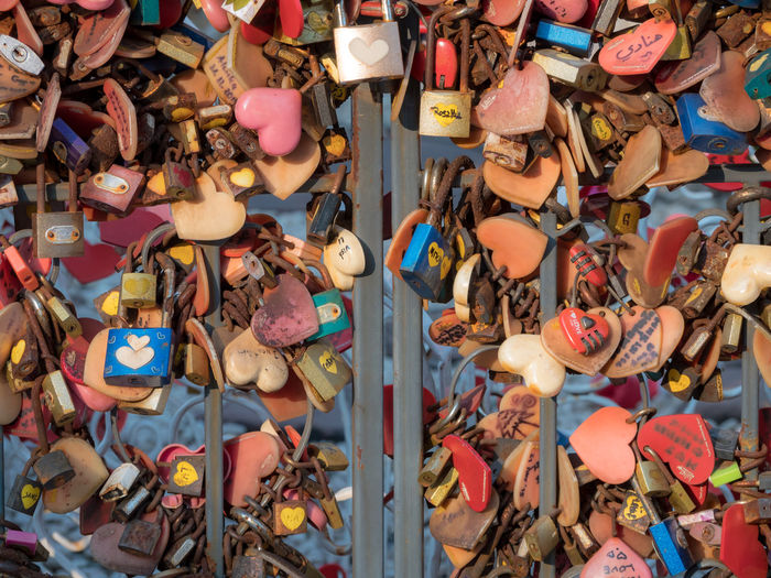 Padlock of lover hang on chain in public park. Some of Asian culture like to promise in love by write both lover names on padlock. They always hang a lock in romantic place. Chain means long relation Fashion Love Lover Padlocks Place Promise Romantic Travel Wall Agreement Backgrounds Belief Cage Choice Communication Cultures Day Full Frame In Love Large Group Of Objects Lock Metal Multi Colored Outdoors Trend