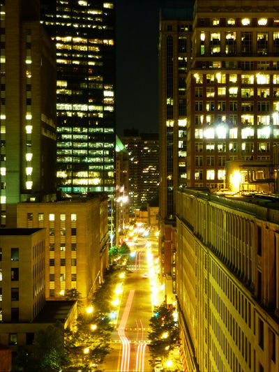Illuminated street amidst buildings in city at night