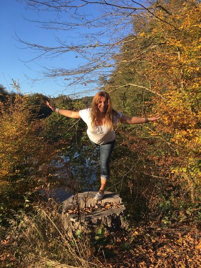 Full Length Of Smiling Woman Balancing On Tree Stump In Forest