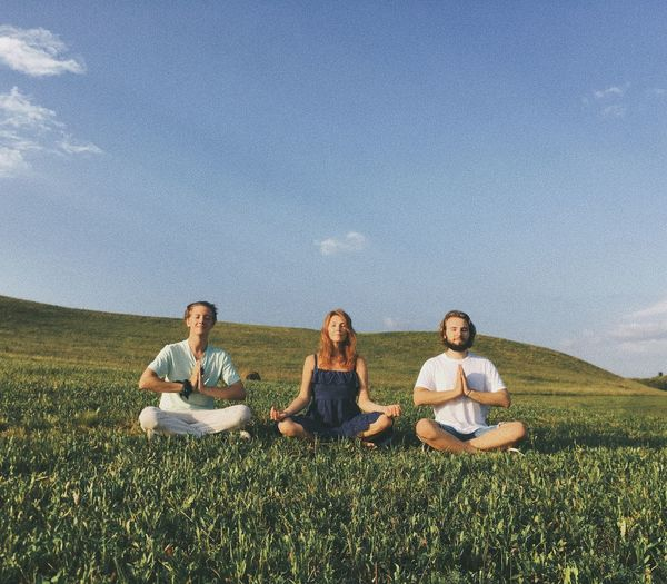 Friends practicing yoga on grassy field