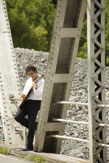 Side view of man playing guitar while standing on covered bridge