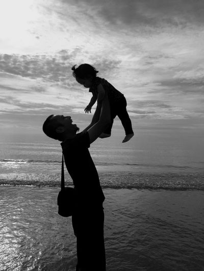 Side view of silhouette man carrying baby girl at beach against sky
