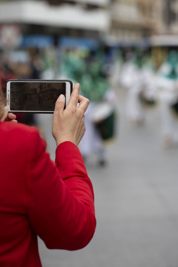 Midsection of woman photographing with mobile phone in city