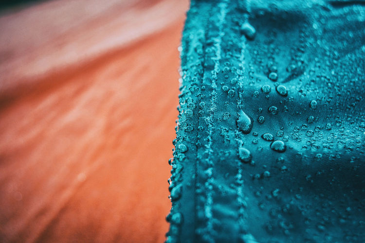 Full frame shot of raindrops on blue glass
