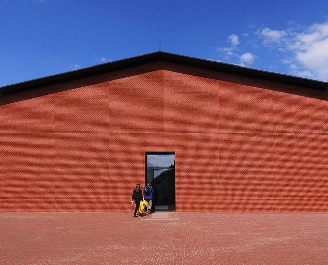 Full length of man walking by building against sky