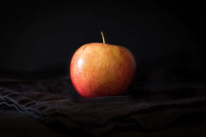 Close-up of apple on table against black background