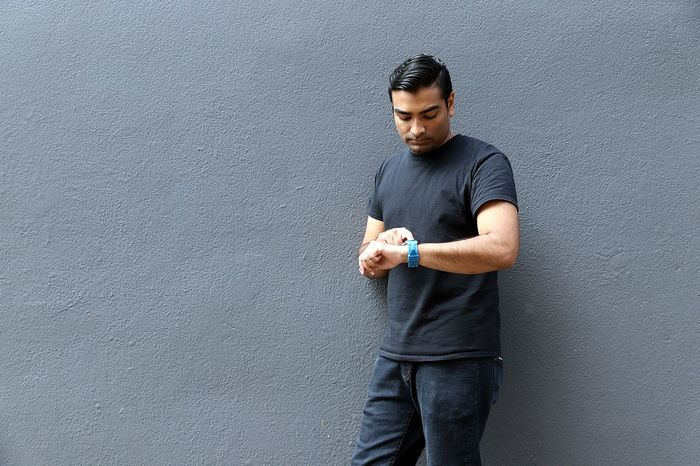 Young handsome man standing against grey wall pointing at smart watch Active American Backgrounds Black Business Man Businessman College Cool Eyebrow Gray Grey Hairstyle Handsome Hipster Indian Intelligence Pointing Popular Portrait Smart Smart Watch Student Tech Technology Watch