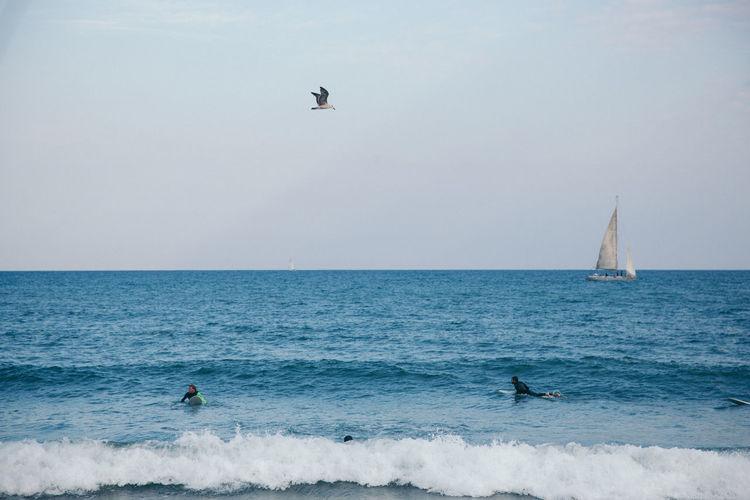 People surfboarding in sea against sky