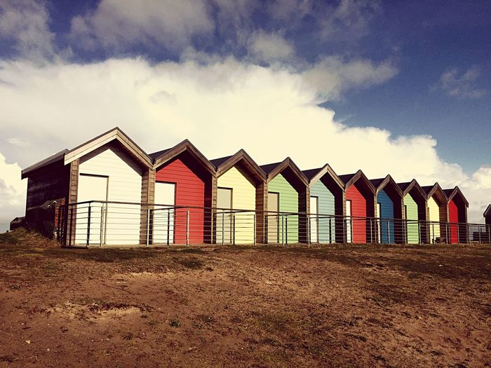 Beach Huts Against Cloudy Sky