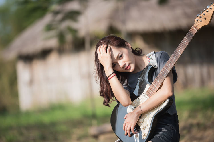 Portrait of young woman holding electric guitar while sitting on audio equipment
