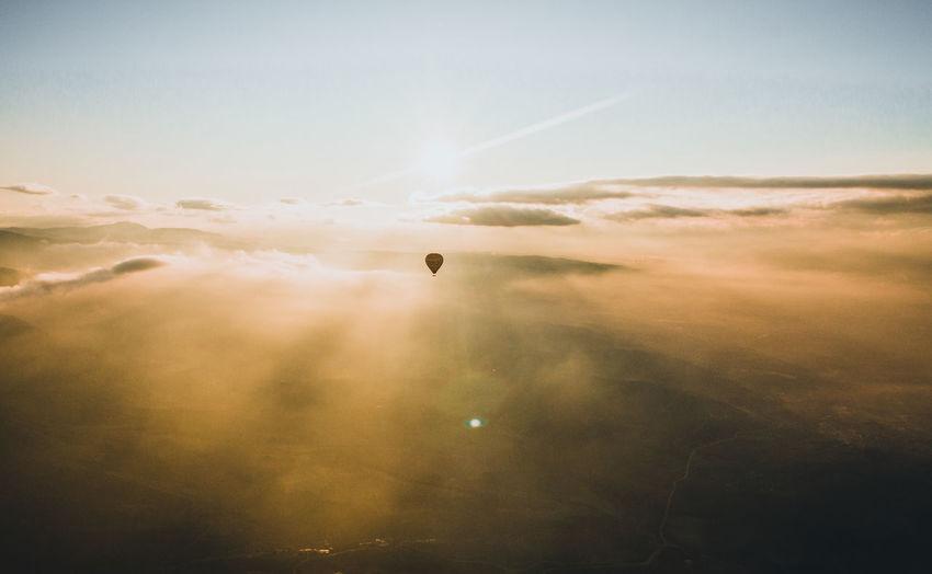 Hot air balloon flying over foggy landscape against sky during sunrise