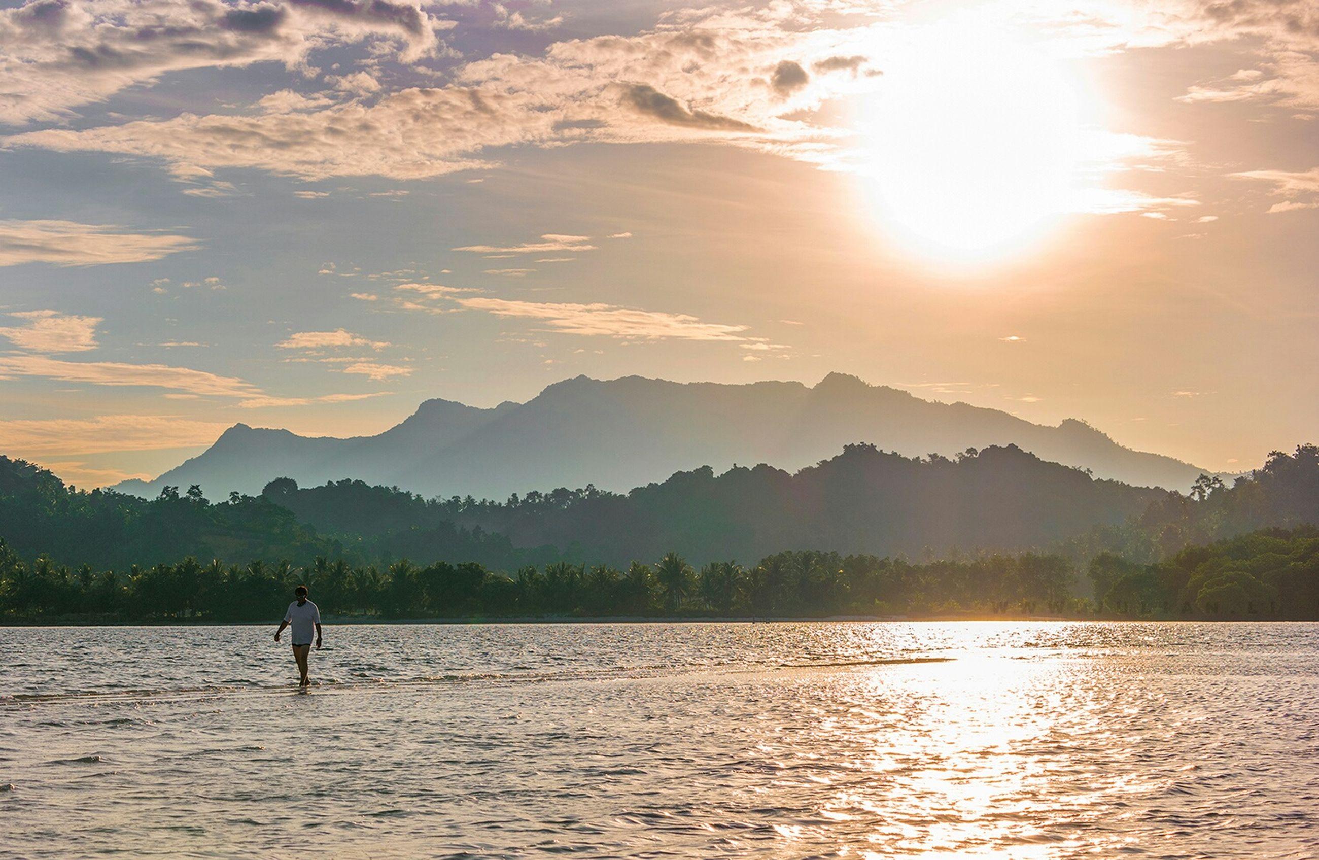 water, mountain, sunset, tranquil scene, scenics, tranquility, silhouette, sun, lake, beauty in nature, waterfront, sky, mountain range, reflection, nature, rippled, sunlight, idyllic, river, sunbeam