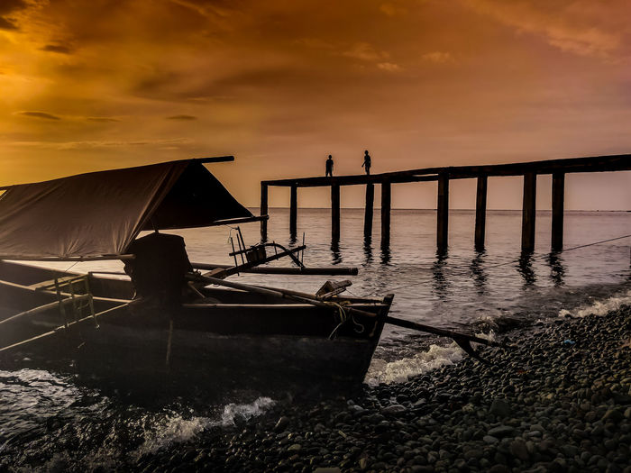 Silhouette boat moored on beach against sky during sunset