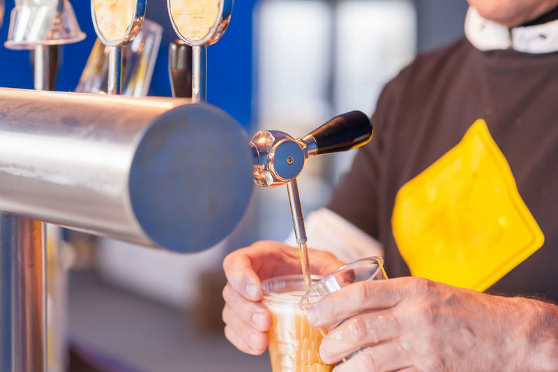 Cropped Hands Pouring Beer From Tap In Glass