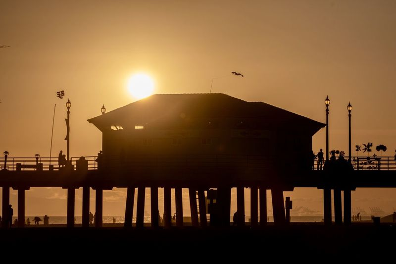 silhouette of the Huntington Beach Pier during sunset Sunset Silhouette Sky Sun Orange Color Built Structure Architecture Nature Sunlight Water Building Exterior Outdoors Clear Sky Huntington Beach Southern California Orange County