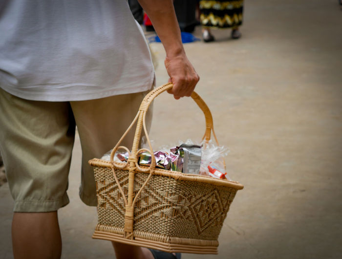 Midsection of man holding basket outdoors