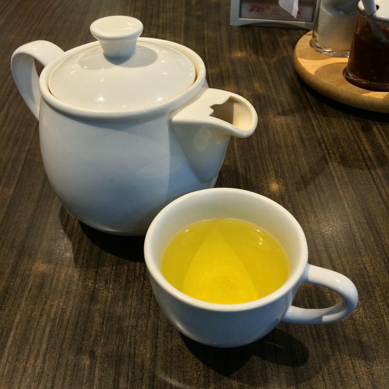 Close-Up Of Chamomile Tea In Cup With Teapot On Table