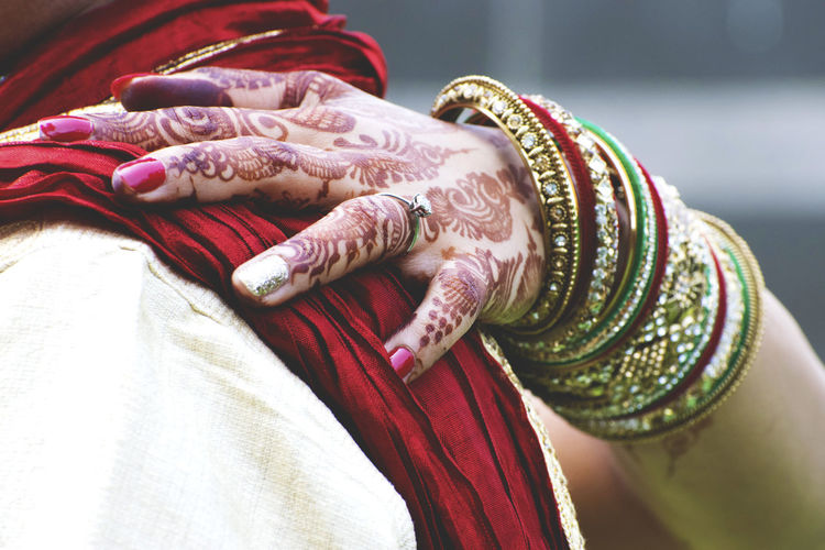 Close-Up Of Woman Wearing Bangles And Henna Tattoo With Arm Around Man