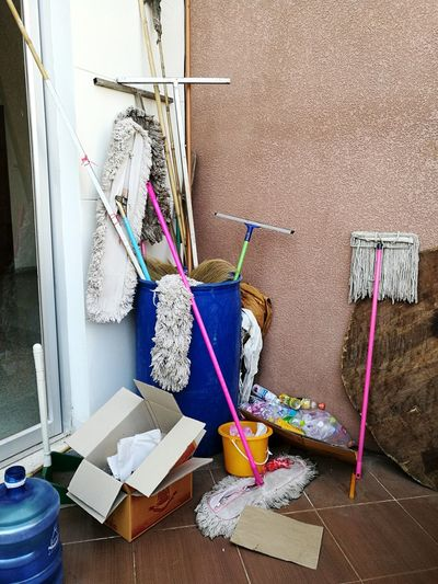 Various mops in container against wall